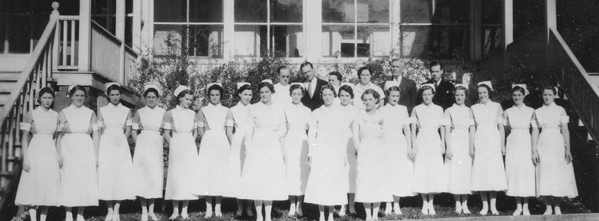nurses in front of old hospital