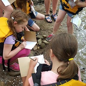 Girl Scouts examining sediment in river