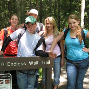 students pose at a trailhead sign