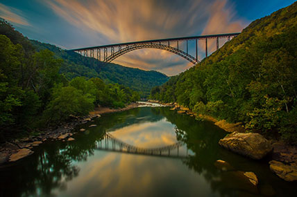 clouds and sunrise behind the New River Gorge Bridge