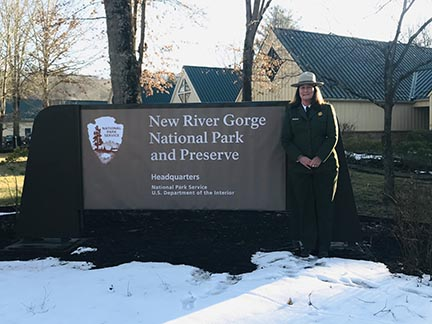 Park ranger in front of park sign