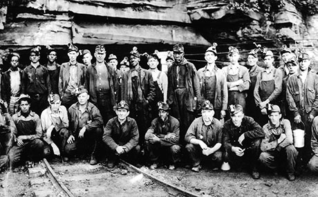 coal miners pose in front of mine