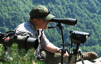 Wildlife biologist using spotting scope to monitor peregrine falcon activity.