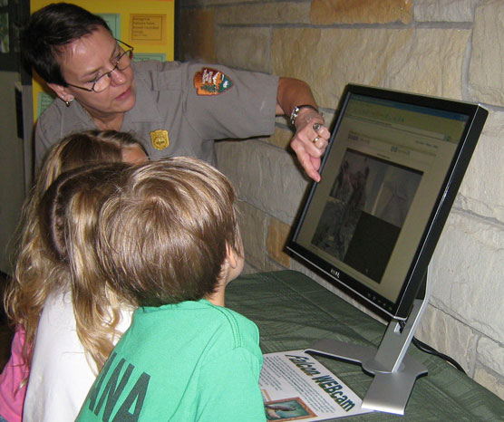 Ranger and young park visitor looking at video of peregrine program.