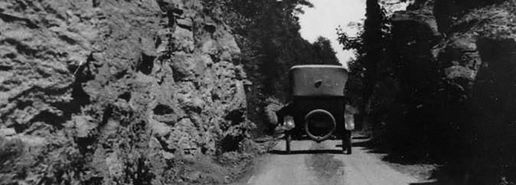 historic photo of old car on dirt road