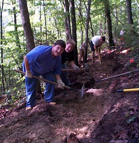 Volunteers hard at work usign handtools to bench in a new section of trail