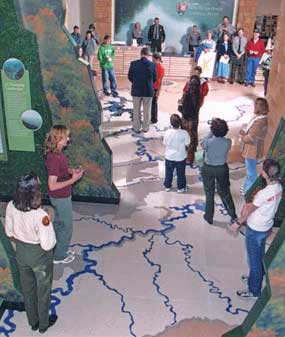 Visitors and watershed floor map inside Sandstone Visitor Center