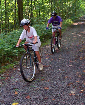 Two bicyclists riding on gravel/dirt trail