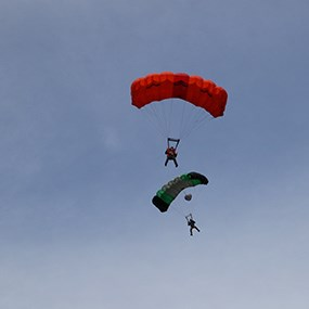 two base jumpers against a blue sky