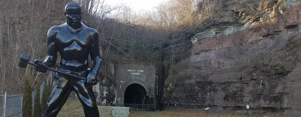 John Henry statue in front of old railroad tunnel