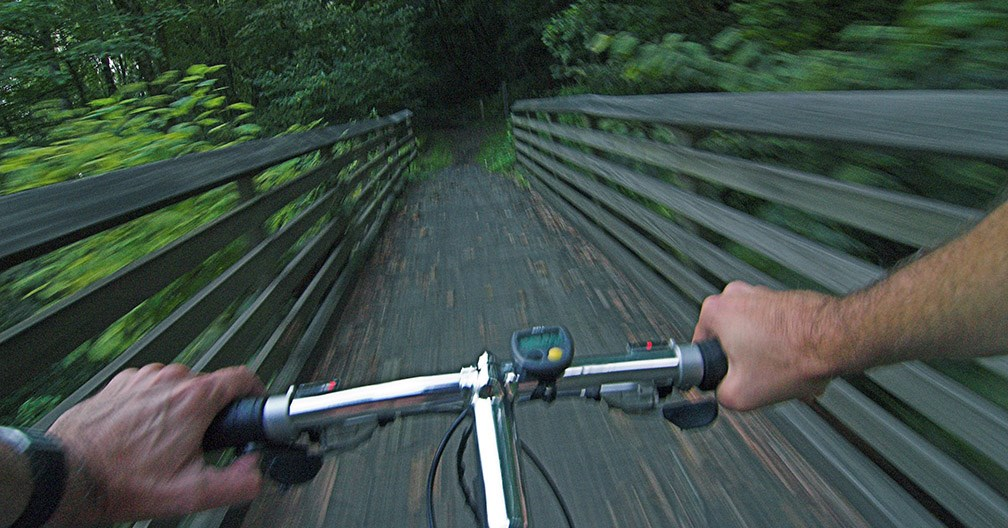 Biker grips the handlebars while mountain biking on a trail