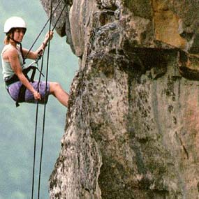 woman rappelling down cliff