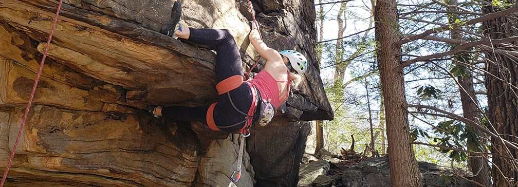 girl rock climbing on overhanging cliff