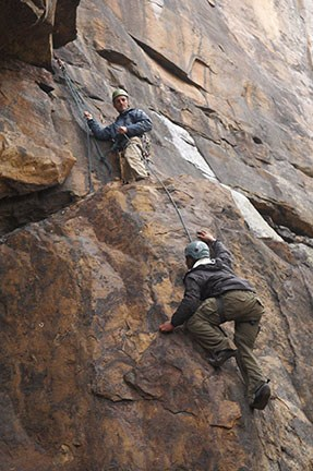 climbers scaling a cliff