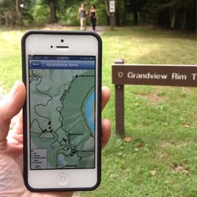 hand holding smart phone with park trails app