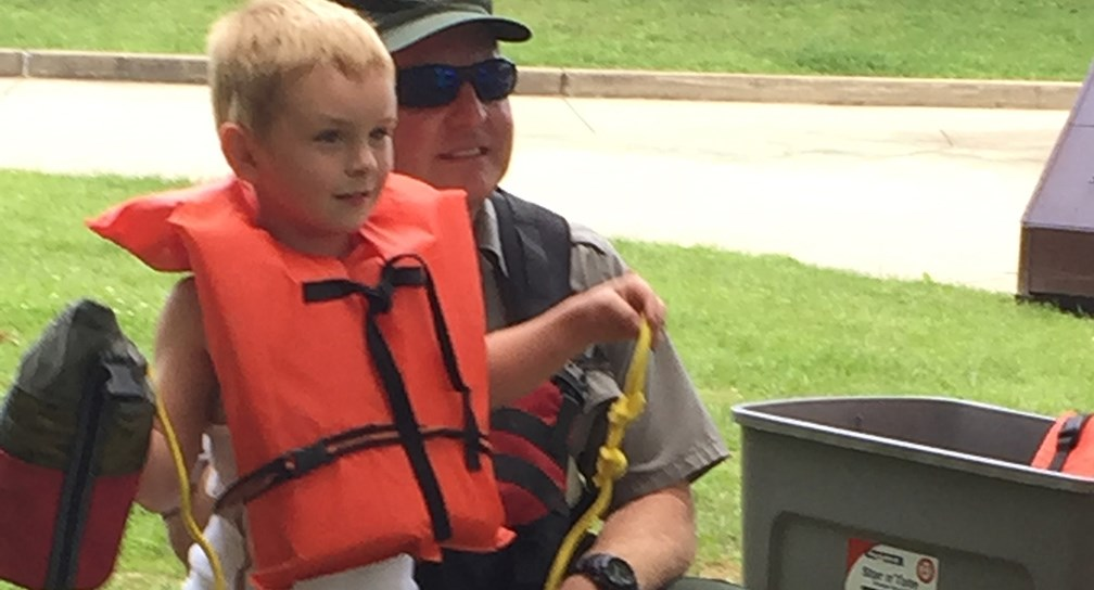 ranger teaching child about life jackets