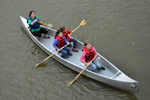 A volunteer helps three girls paddle a canoe down the Niobrara NSR.