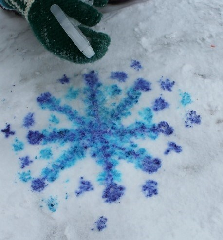 a blue snow flake painted on white snow