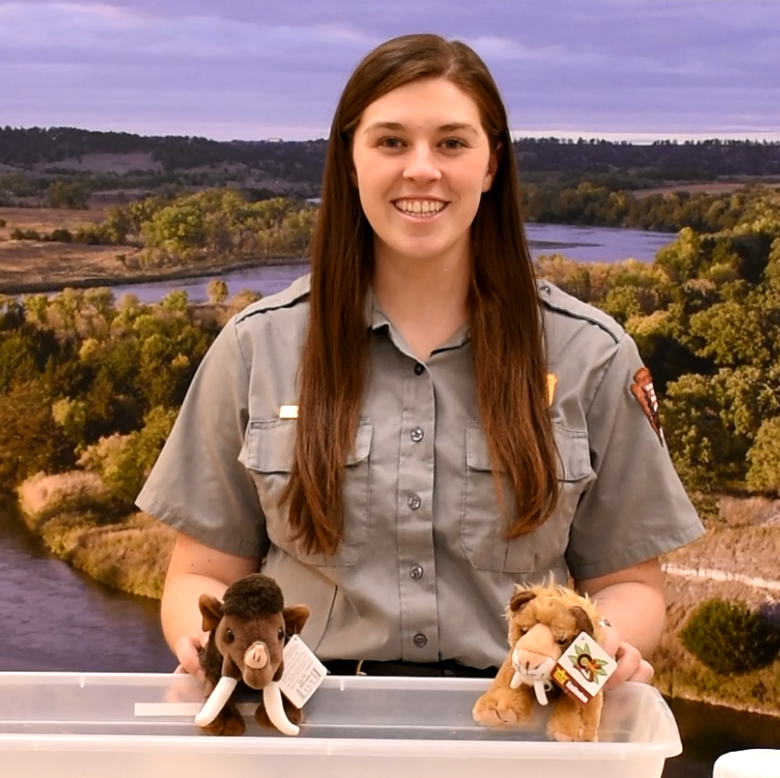 A Ranger holds two stuffed animals while presenting.