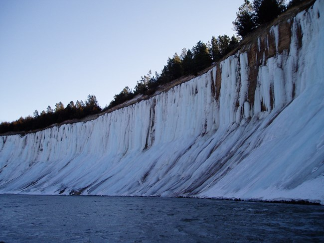 Groundwater seeps through bluff walls, freezing into curtains of ice that stretch down into the river.