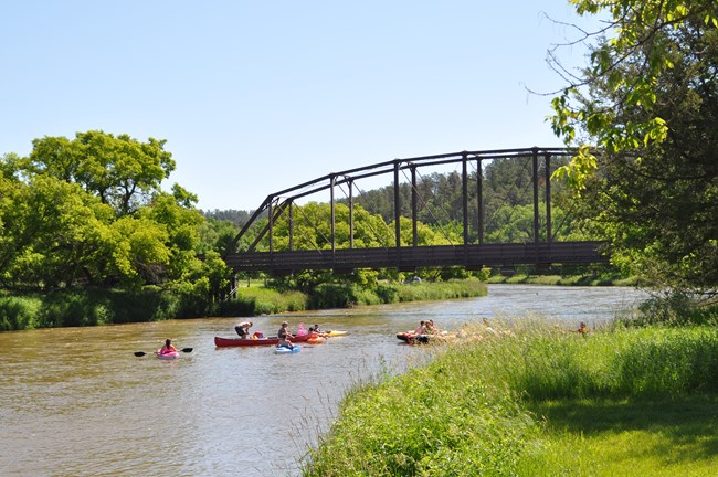 Canoes coming around a river bend, a bridge in the background.