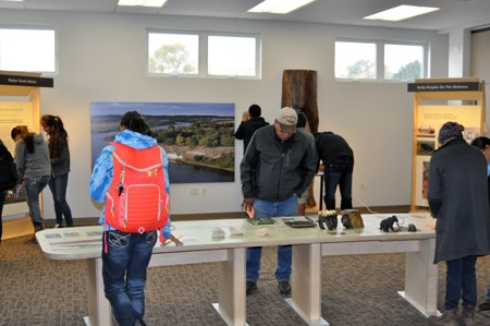 Visitors look at exhibits in the visitor center, including a hands on table.