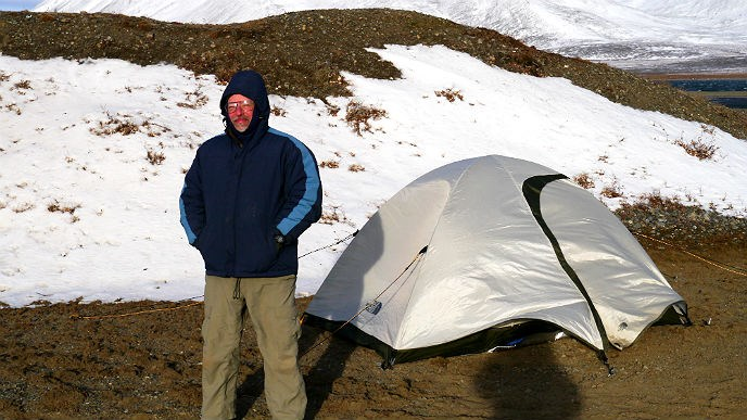 Man standing in front of tent with snow on the grond