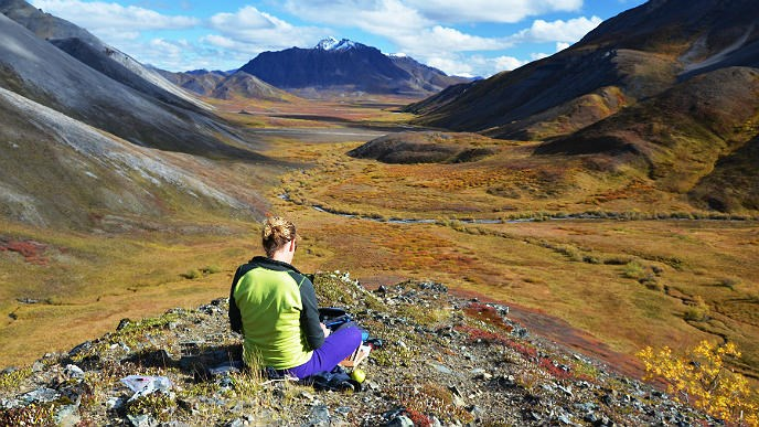 Woman sits on a rock and looks out at a mountain-ringed valley