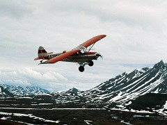 Small red airplane flying through the mountains