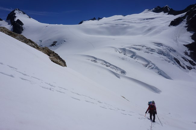 A North Cascades National Park Ranger ascends to the Colonial/Neve Col from the Neve Glacier