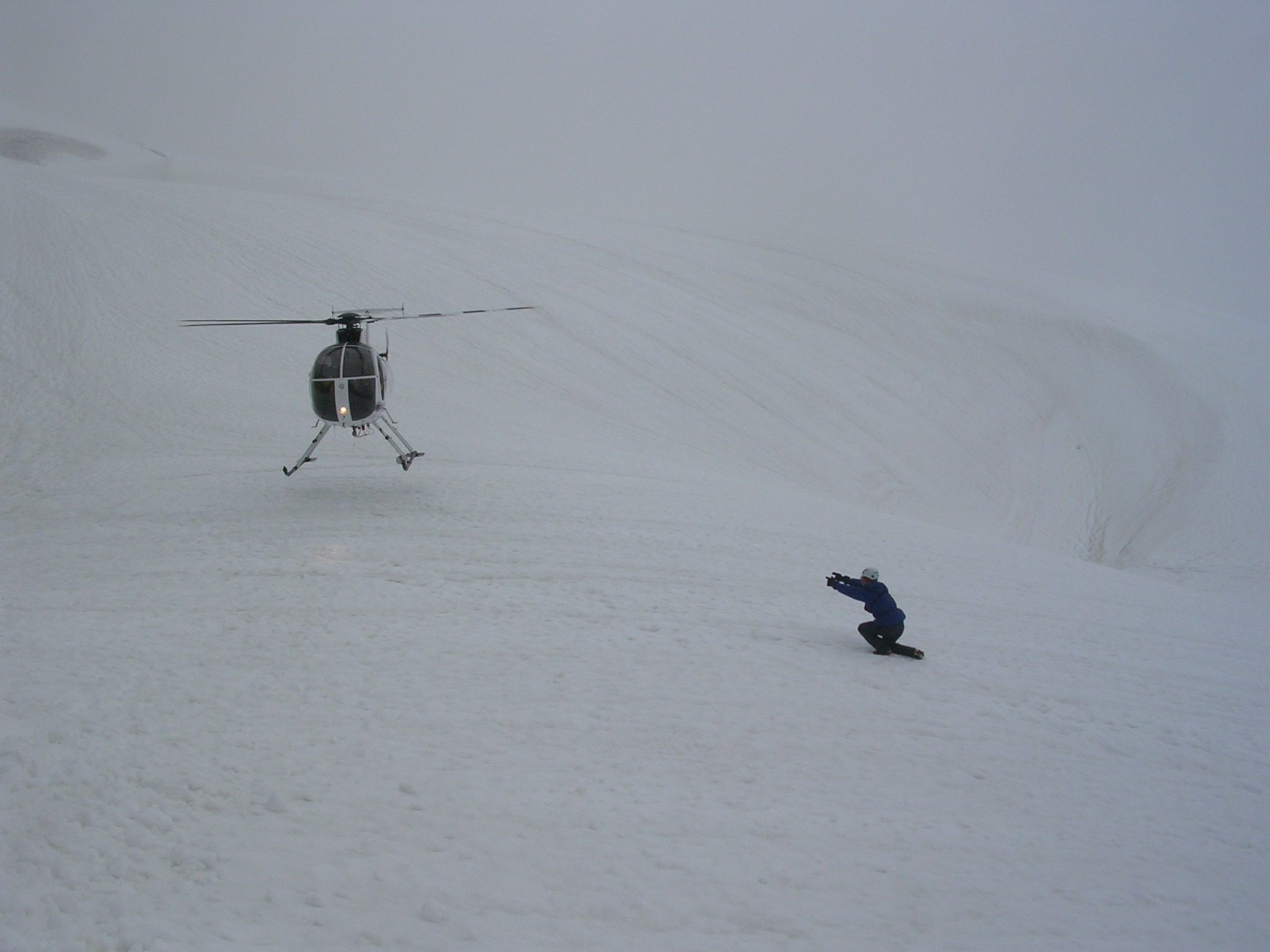 Helicopter landing in fog on glacier with person directing the landing