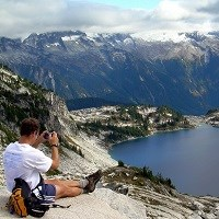 A hiker sits and photographs a mountain lake.