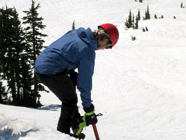 Using an ice axe to descend steep snow