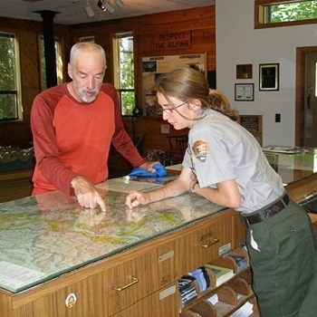A ranger and park visitor look at a map on the counter.