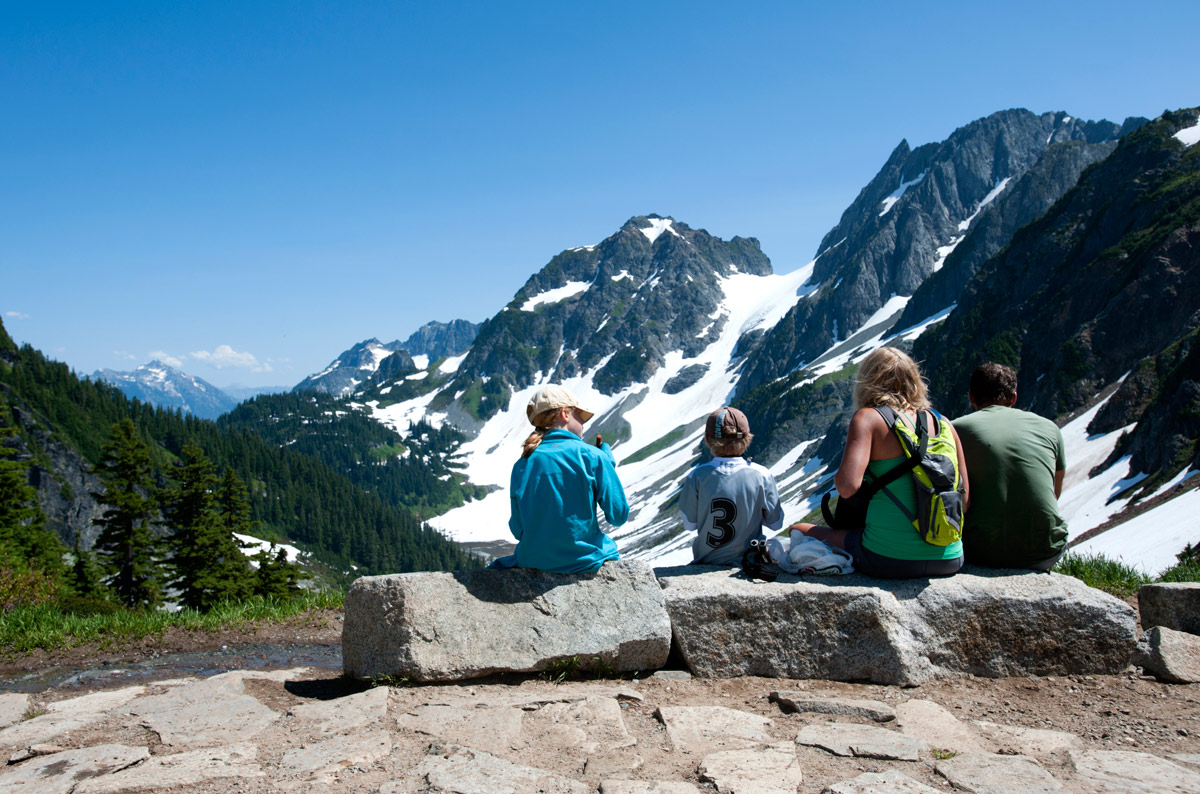 Family resting together at Cascade Pass. NPS/Deby Dixon