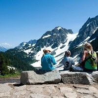 Hikers rest on a bench with mountain views.