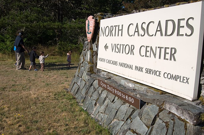 Morning bird hike participants walk past the North Cascades Visitor Center sign. Image Credit: NPS/NOCA/David Snyder