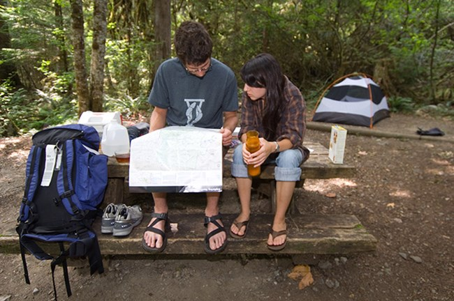 A young man and woman consult a map in their campsite at the Colonial Creek Campground before taking a day hike. Photo Credit: NPS/David Snyder