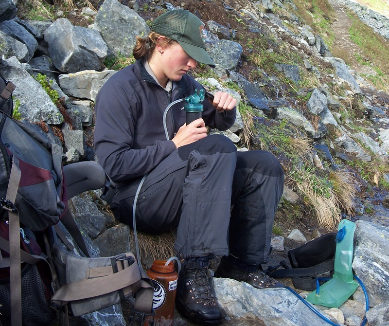 Hiker treating drinking water using portable filter
