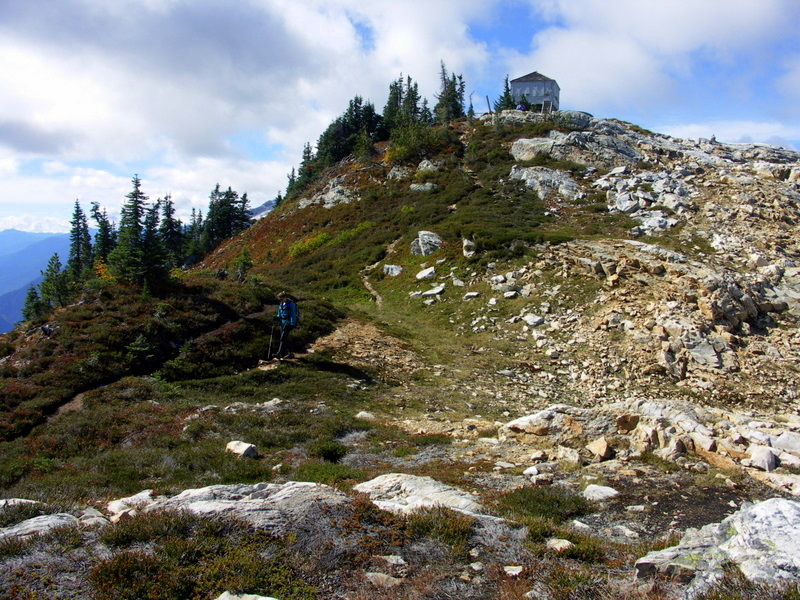A hiker below Sourdough Mountain Lookout, heading toward Pierce Mountain