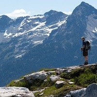A hiker stands in front of a mountain view.