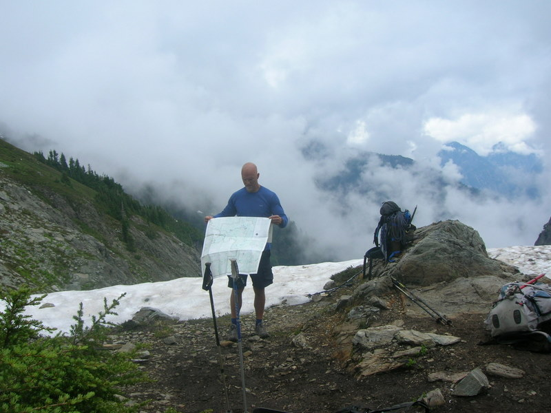 Hiker looking at map with clouds moving in