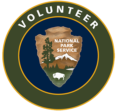 "National Park Service Arrowhead on a field of blue with a green circle around it. Text in the green circle reads ""Volunteer."""