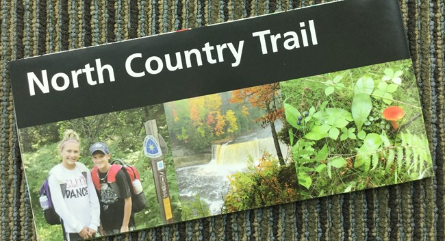 Front cover of the North Country Trail brochure shows the trail name in a black title band with three photos below. The three photos show to young hikers, a waterfall, and small forest floor plants.