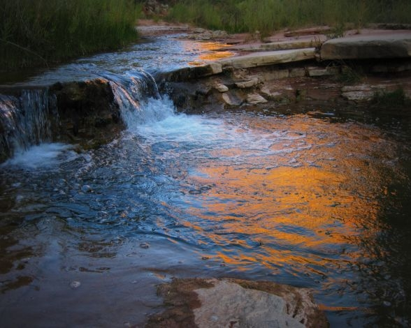 Creek water flows over a small shelf as it reflects orange light