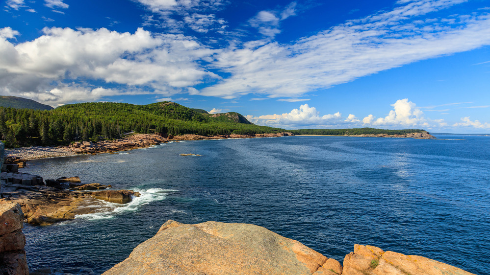Rocky Maine coast on left with bright blue ocean on right. Coast line seen in the distance covered in large evergreen trees.