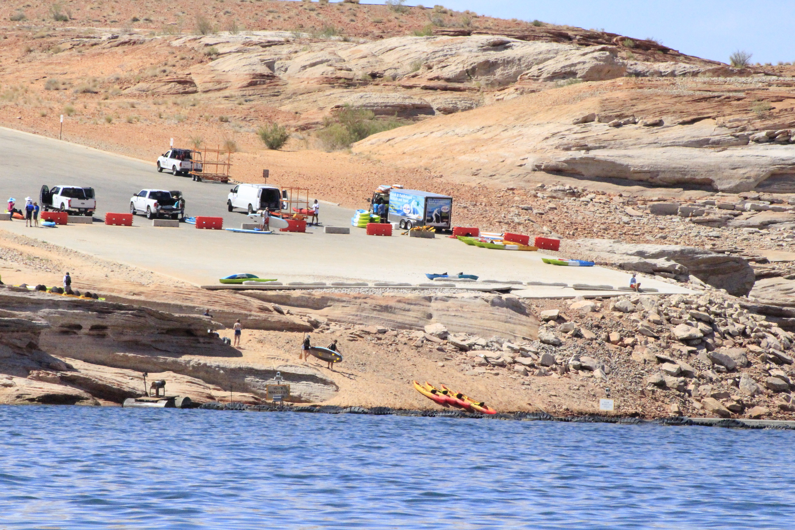 Trucks unloading kayaks on a barricaded launch ramp as visitors descend a rocky shoreline.