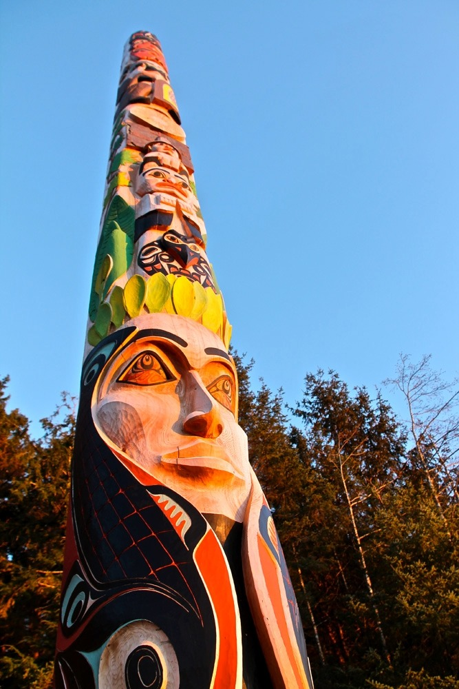 Totem pole painted with a variety of vivid colors – red, yellow, green, blue, black, and turquoise.