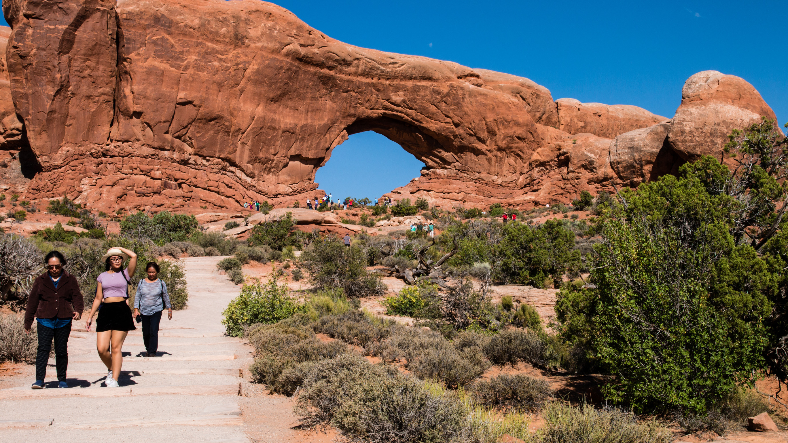 Visitors walk along a paved pathway at Arches National Park. Photo by M. Reed, NPS.