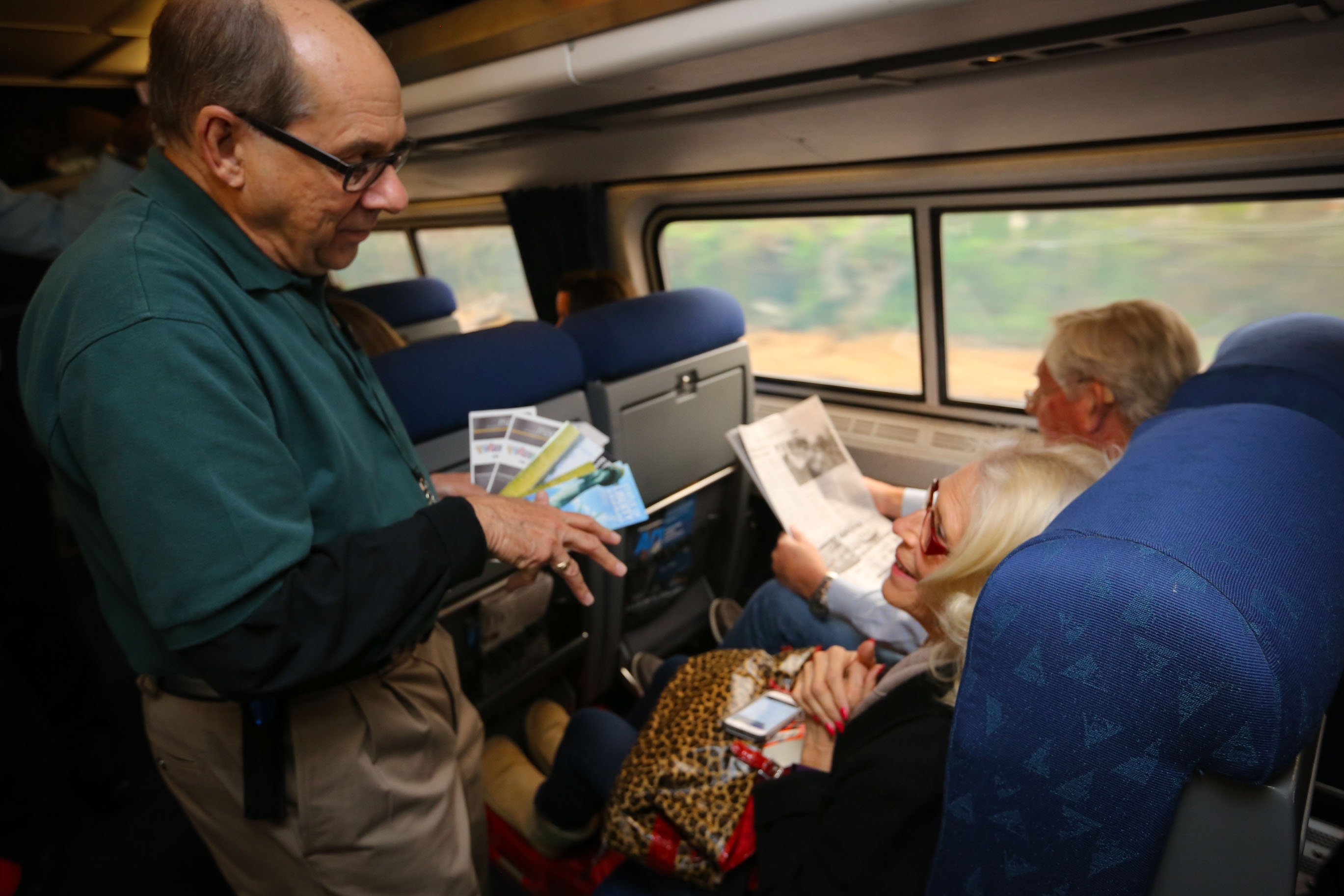 A Trails and Rails volunteer helps Amtrak passengers find their parks during the National Park Service Centennial year.